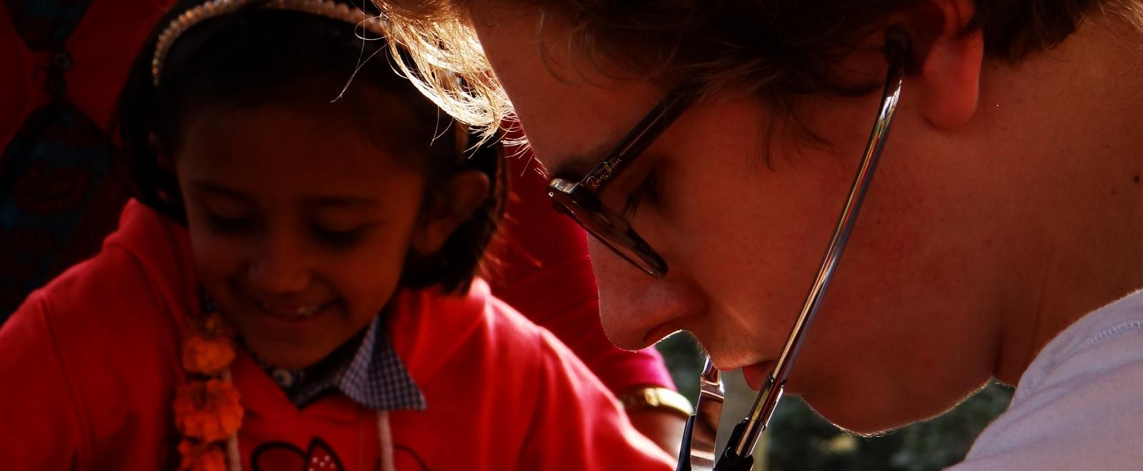 A female intern from Projects Abroad is pictured treating a child using a stethoscope on her nursing intership in Nepal.